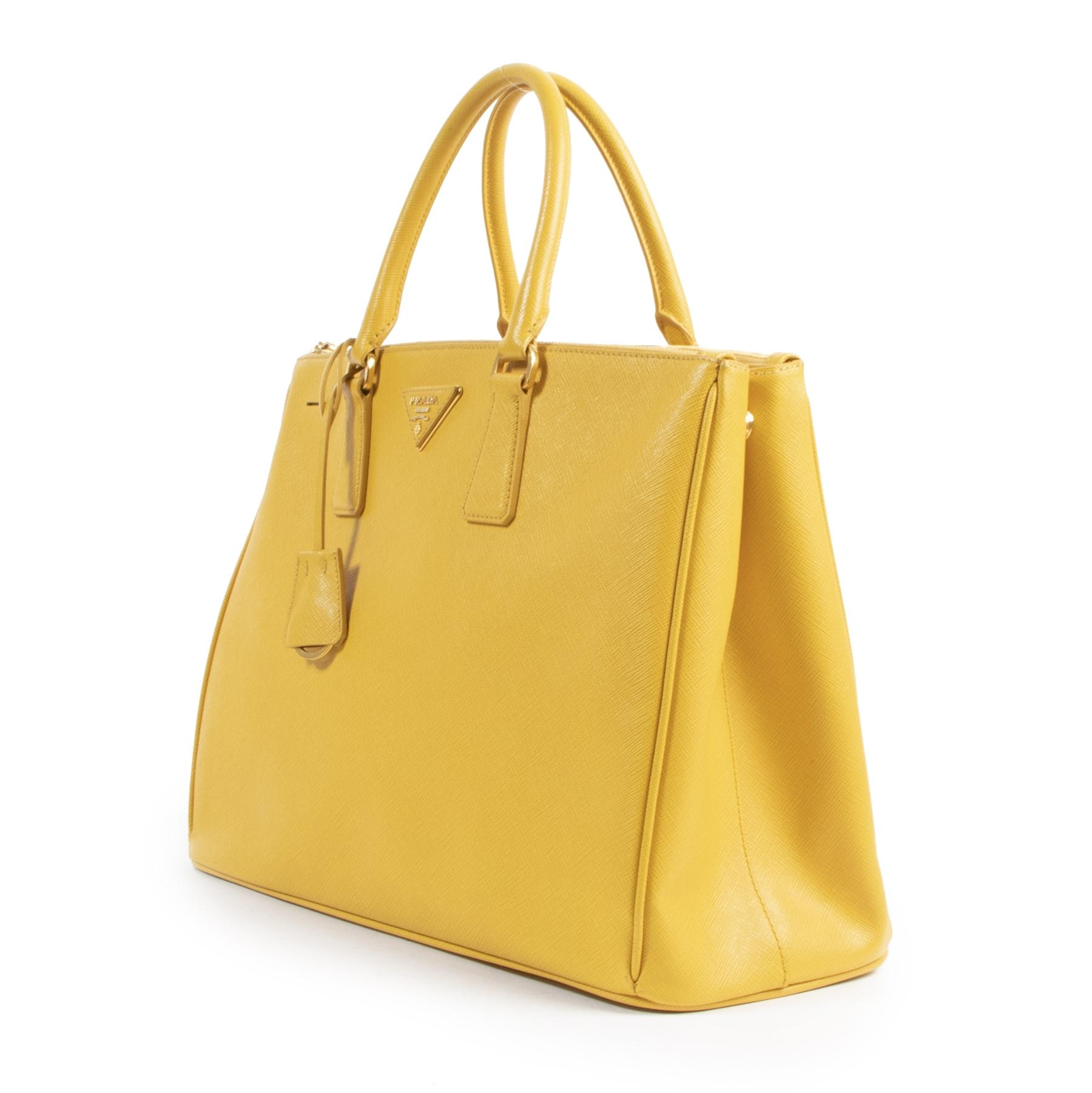 Tweedehands designer handtassen en accessoires te koop bij Labellov zoals deze Prada Yellow Double Zip Top Handle Tote