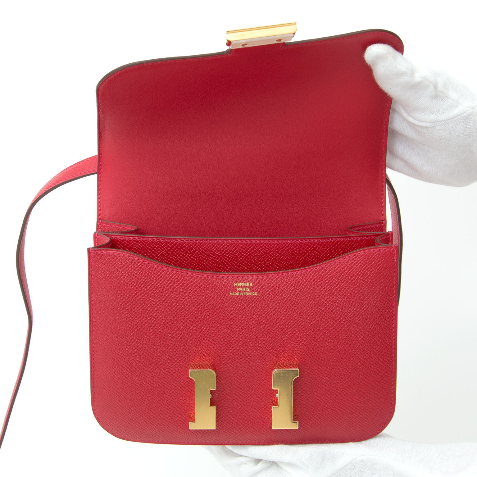 This little gem is the Hermès Mini Constance III in Epsom leather in 'Rouge Casaque', a red hue as vibrant as you can get!  It is not a classic deep red! Because of its vibrance, Rouge Casaque has a more playfull, even sexy undertone.  The gold-tone H clo